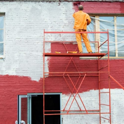Painter painting business building while it's still open
