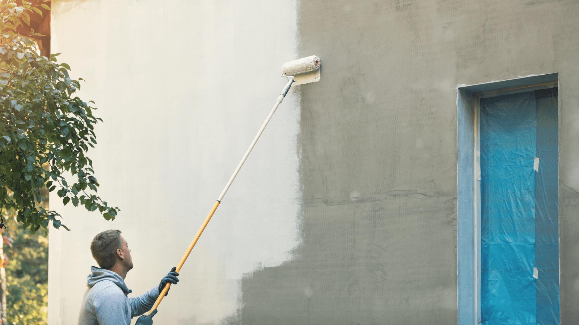 A man doing an exterior home painting job